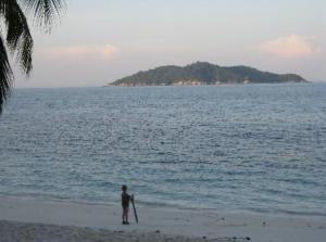 Pieni poika seisoo trooppisen saaren rannassa hiekalla ajopuuhun nojaten ja merelle katsoen.