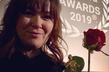 """Heli Järvenpää hymyilee palkintopysti ja ruusu kädessä. Taustalla valkokangas, jossa heijastettuna """"eOppiva Awards 2019"""" -tunnus."""