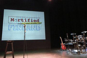 """Esiintymislavalla tyhjä penkki, rummut, mikrofoni ja seinälle heijastettuna teksti """"Mortified Finland""""."""