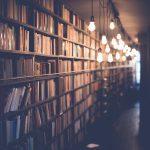 Kirjaston kirjahylly täynnä kirjoja, himmeä iltavalaistus.