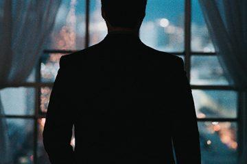 Mies seisoo pimeässä huoneessa vasten ikkunaa, jonka takaa heijastuvat öiset kaupungin valot. Miestä ei tunnista, hän on vain tumma varjo kuvassa.