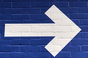 Siniseen tiiliseinään maalattu valkoinen iso nuoli, joka osoittaa suoraan vasemmalta oikealle.